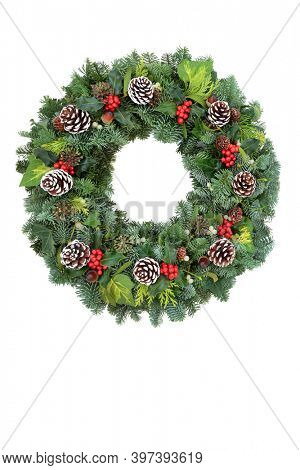 Holly and winter greenery solstice and Christmas wreath on white background with copy space. Traditional composition for the festive holiday season and New Year.