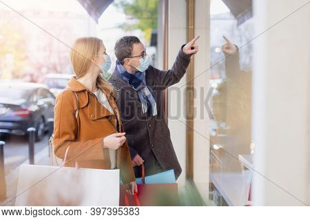 Couple doing shopping during partial lockdown standing in front of shop window with mask