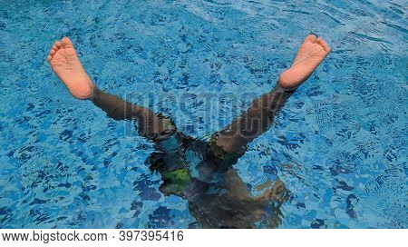 Funny shot of a cute boy feet in swimming pool