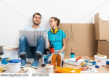 Young Man And Woman Together Planning Their Home Renovation. Cardboard Boxes, Painting Tools And Mat