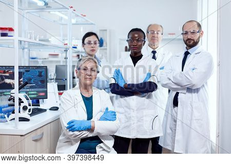 Portrait Of Head Scientific Project Ar Her Research Team Holding Arms Crossed At Workplace. African