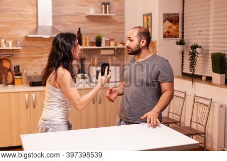 Woman Looking Disappointed At Husband After Catching Him Cheating While Holding Phone. Heated Angry
