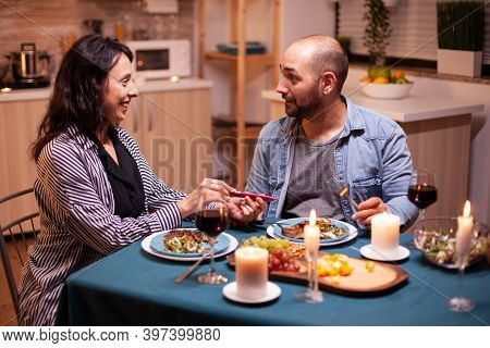 Showing Positive Pregnancy Test To Husband During Romantic Dinner. Excited Couple Smiling, Hugging A