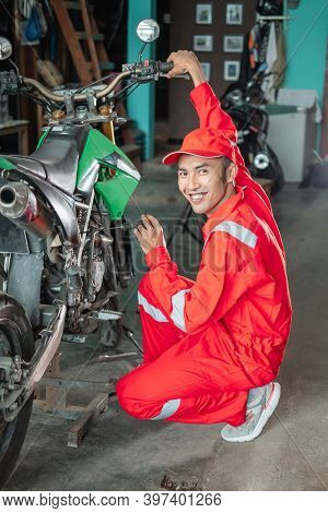 Male Mechanic Smiles While Setting Up The Carburetor Using The Screwdriver Next To The Motorbike