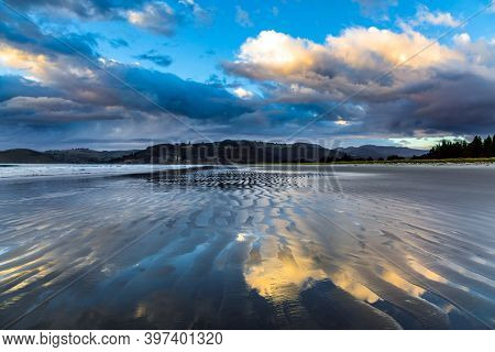 Low tide. Strips of sand and water left by the ocean tide. Sunrise over the ocean. New Zealand, Pacific Coast. The concept of artistic photography. Artistic postal and greeting card