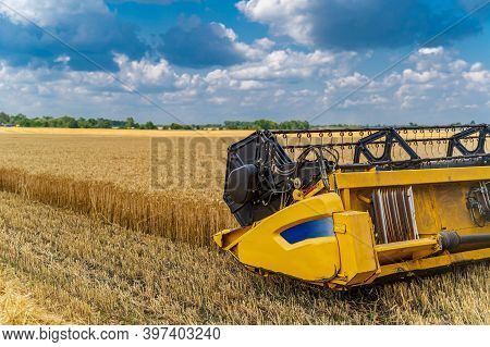 Agricultural Machinery Theme. Combine Harvester At Work Harvesting A Field Of Wheat. Harvesting Mach