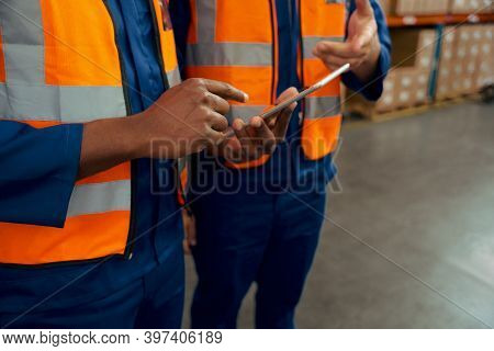 Mid Section Of Two Male Employees Holding Digital Tablet In Manufacturing Industry