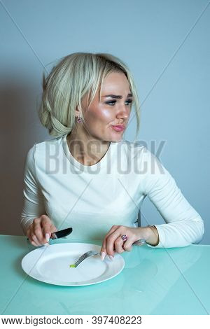 The Girl Is Sick With Anorexia And Eats Little. Girl With A Fork And Spoon Eats A Small Portion Of V