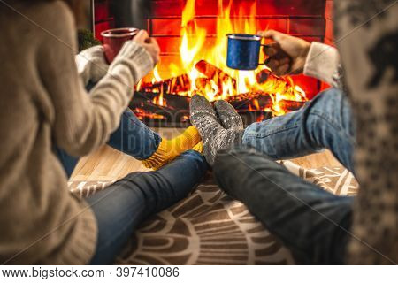 Man And Woman Are Sitting Next To The Fireplace With Cups. Concept Of Creating A Cozy Winter Atmosph