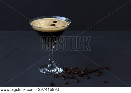 Espresso Martini Cocktail Garnished With Coffee Beans On Dark Table. Martini Glass On A Black Backgr