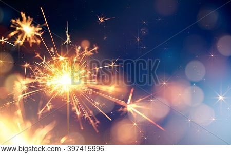 Glittering Sparkler Against Bokeh Light Background With Copy Space