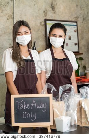 Portrait of waitress wear protective face mask smiling with take away or takeout food sign. This essential service is very popular while city lockdown from coronavirus COVID-19 Pandemic