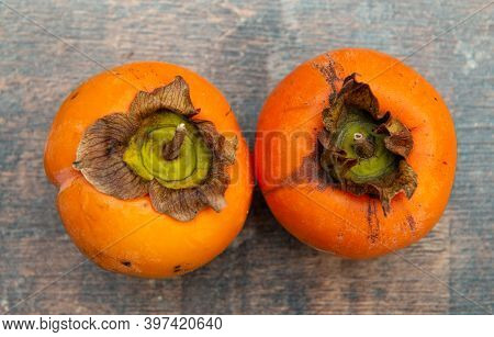 Persimmon Fruit On Old Wooden Background, A Top View