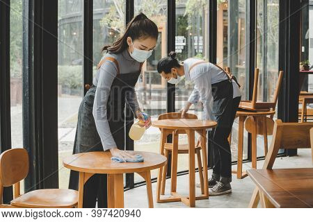 Asian Waitress Staff Wearing Protection Face Mask In Apron Cleaning Table With Disinfectant Spray Fo