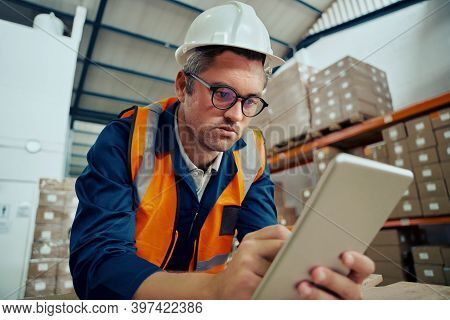 Portrait Of A Male Warehouse Worker Looking At Digital Tablet Screen In Industrial Warehouse