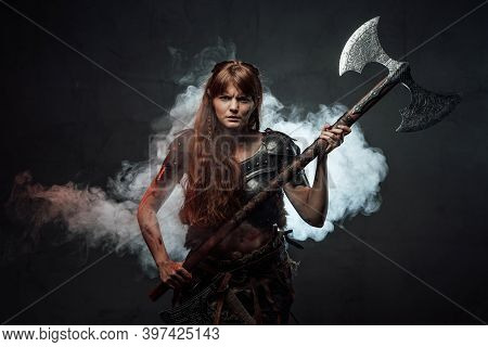 Violent And Savage Scandinavian Female Warrior Holding Huge Two Handed Axe In Dark Foggy Background.