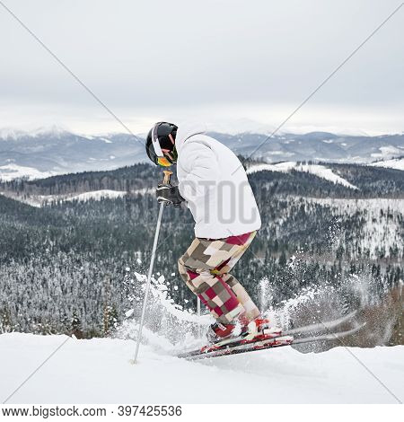 Back View Of Alpine Skier In Jacket And Helmet Skiing On Fresh Powder Snow In Winter Mountains. Man