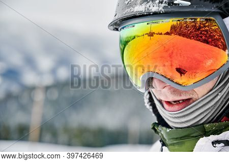 Close-up Cropped Snapshot Of Man Wearing Ski Goggles With Reflection Of Snowed Slope. Bright Glasses