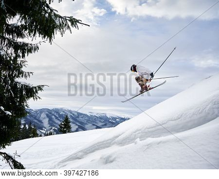 Side View Of Male Skier Making Jump While Sliding Down Snow-covered Slope On Skis Under Beautiful Cl