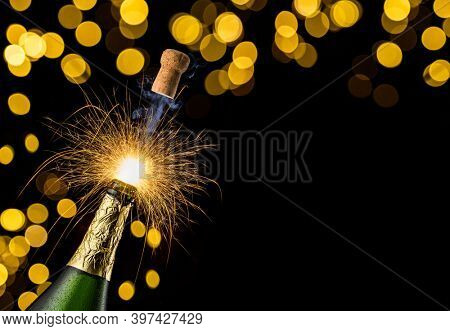 Cork flies out of a bottle of champagne and a sparkler burns, black background with yellow Christmas lights.
