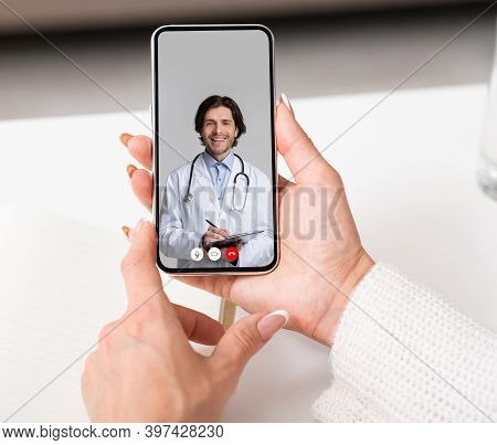 Sick Lady Talking With Doctor Online Via Video Call On Smartphone Sitting At Home. Physician Consult