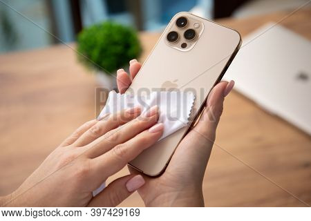 Alanya, Turkey - November 26, 2020: Woman Hand Holding Apple Iphone 12 Pro Max Gold And Rubs It With
