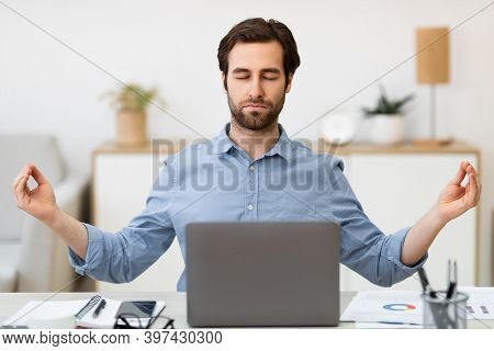 Keep Calm. Businessman Meditating In Office, Sitting At Laptop With Eyes Closed Relaxing For Work St