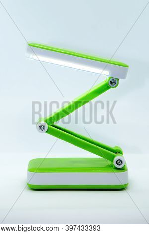 Compact Foldable Portable Led Desk Lamp With Flexible Body Made Of Bright Green Plastic On White Bac