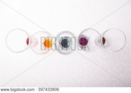 Glass Transparent Round Containers Placed In A Row On A White Table With Food Coloring Powder Of Dif