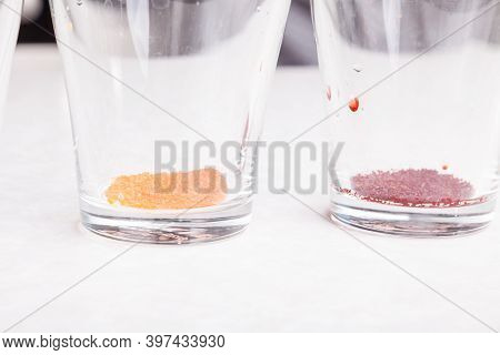Close-up Of Colored Powders Of Yellow And Red Color Poured On The Bottom Of Transparent Glasses On A
