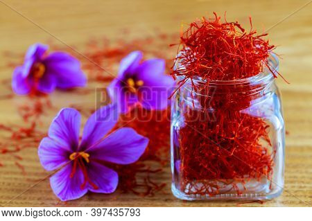 Stigmas Of Saffron Are Scattered On A Wooden Surface And In A Glass Bottle. Saffron Crocus Flowers.