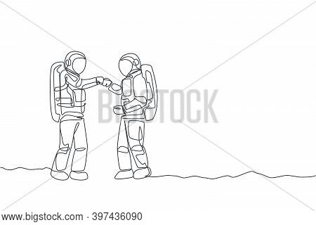 One Continuous Line Drawing Of Young Happy Astronaut Giving Fist Bump Gesture To His Friend In Moon