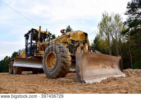 Motor Grader On Road Construction In Forest Area. Greyder Leveling The Sand, Ground And Gravel Durin
