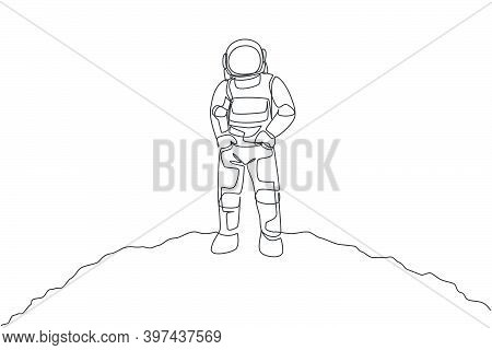 One Continuous Line Drawing Of Young Spaceman On Spacesuit Put Hands In Pockets In Moon Surface. Ast