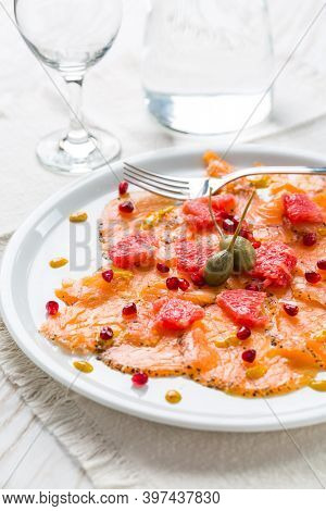 Salmon carpaccio with pink grapefruit and pomegranate on white plate