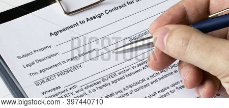 A Man's Hand With A Pen Signs A Contract In A Folder