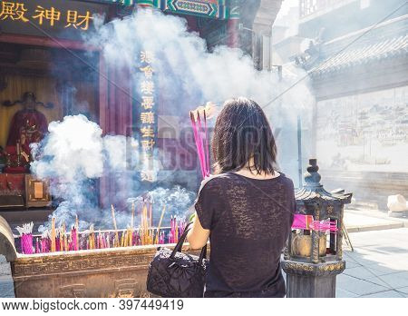 Young Woman Holding Large Burning Incense Sticks While Praying At The Taoist Temple Of The Queen Of