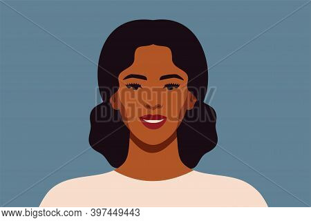 Black Woman With Curly Hair In A Bunch Smiles And Looks Directly. Confident Young Female With Brown