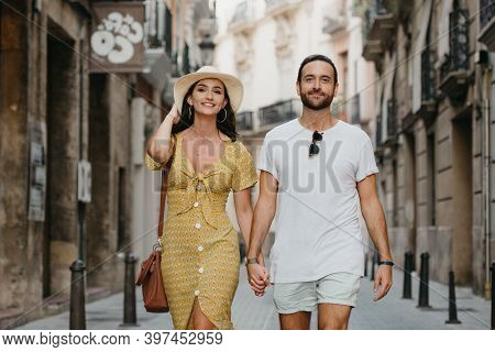 A Girl In A Yellow Dress With A Plunging Neckline And Her Boyfriend With A Beard Are Walking In Old