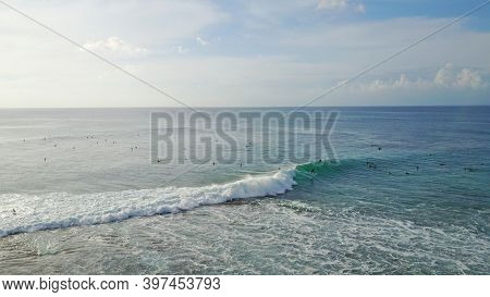 Surfers Catch Waves At Uluwatu Beach, Bali. Huge Waves Stretch Along The Beach. A Lot Of People With