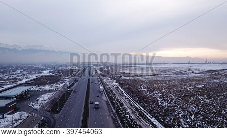 A Large Truck Is Traveling On A Multi-lane Highway. Around The Steppe, Snow And Emptiness. Cloudy We