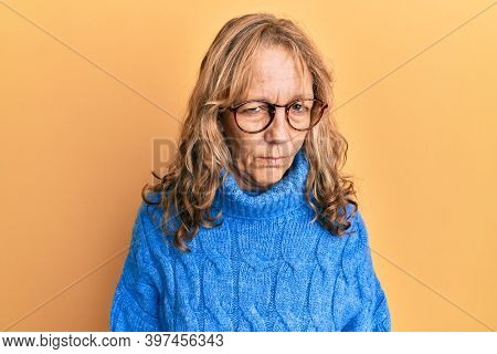 Middle age blonde woman wearing glasses and casual winter sweater skeptic and nervous, frowning upset because of problem. negative person.