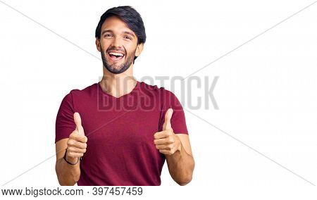 Handsome hispanic man wearing casual clothes success sign doing positive gesture with hand, thumbs up smiling and happy. cheerful expression and winner gesture.