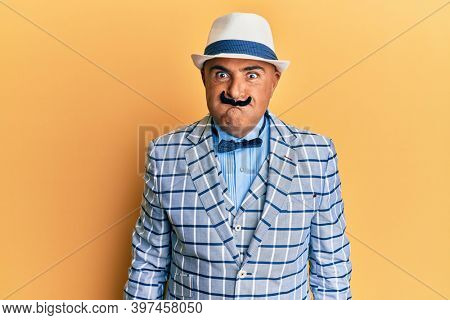Mature middle east man with mustache wearing vintage and elegant fashion style puffing cheeks with funny face. mouth inflated with air, crazy expression.