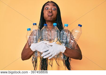 African american woman with braids holding recycling plastic bottles puffing cheeks with funny face. mouth inflated with air, catching air.