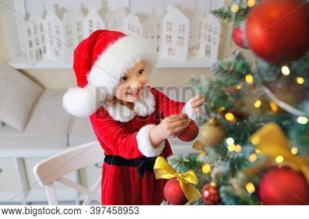 A Girl In A Santa\\\'s Helper Hat And A Respiratory Protection Mask And Gloves Is Packing Gifts On C