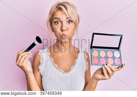 Young blonde girl holding makeup brush and blush puffing cheeks with funny face. mouth inflated with air, catching air.