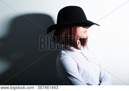Mysterious fashion young woman in black hat and white shirt, copy space where can the advertising message be written
