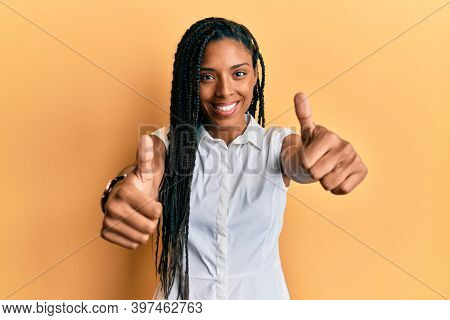 African american woman wearing casual clothes approving doing positive gesture with hand, thumbs up smiling and happy for success. winner gesture.