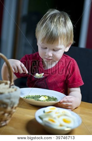 Young Boy Eating Spinach Soup With Egg